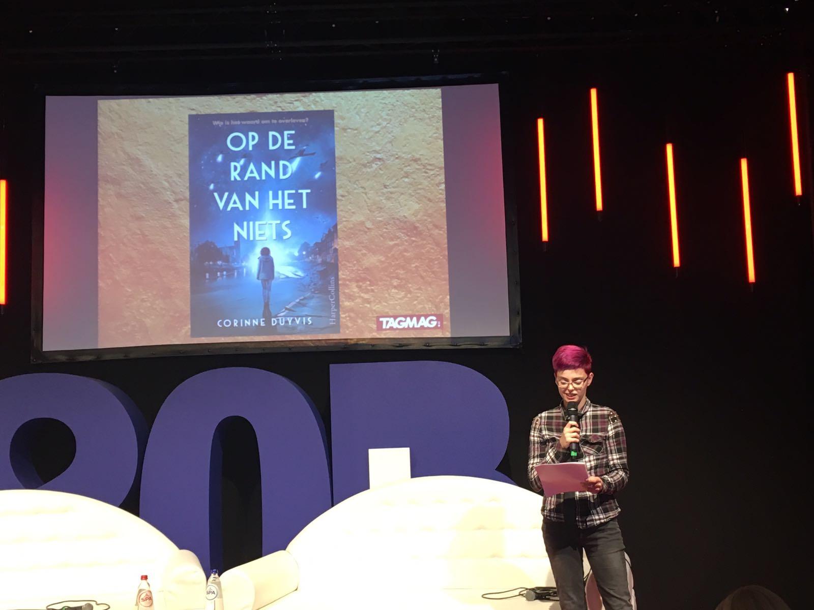 Corinne leest op een podium voor uit haar boek; achter haar wordt de omslag geprojecteerd op een scherm.